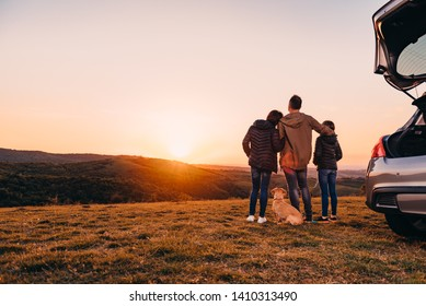 Family with small yellow dog embracing at hill and looking at sunset