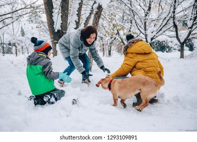 Family with a small yellow dog making snowman
