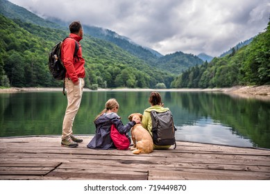 Family with small yellow dog resting on a pier and looking at lake and foggy mountains