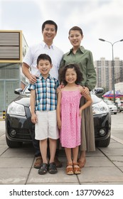 Family smiling in front of the car, portrait