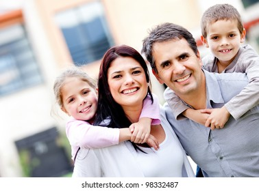 Family smiling and parents carrying kids outdoors