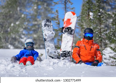 Family of snowboarders on top of a mountain on a sunny day with snowboards. Concept of snowboarding. Ski resort Sheregesh.