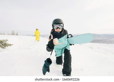 Family of snowboarders playing and have fun in snow on mountain top. Sunny holiday in ski resort