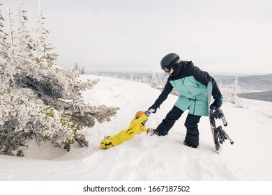 Family of snowboarders playing in snow on mountain top, parents help child out of tree. Sunny holiday in ski resort
