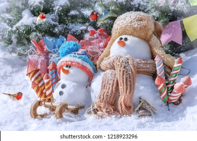 Family of snowmen with fireworks on the background of a winter landscape on a sunny day