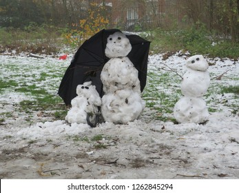 a family of snowmen hidingunder an umbrella in the Vondelpark in Amsterdam