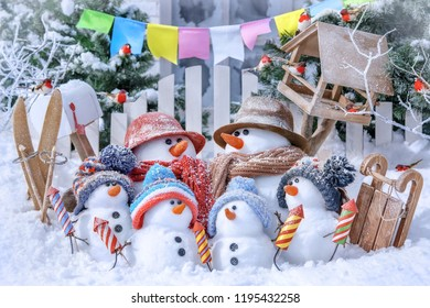 Family of snowmen on skis and sledges in the background of a winter landscape on a sunny day