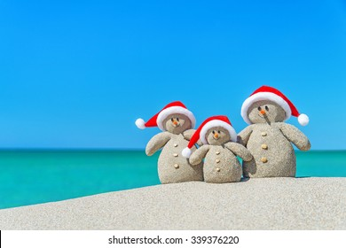 Family of Snowmen in santa hats at tropical beach. New Year's and Christmas holiday in hot countries concept.