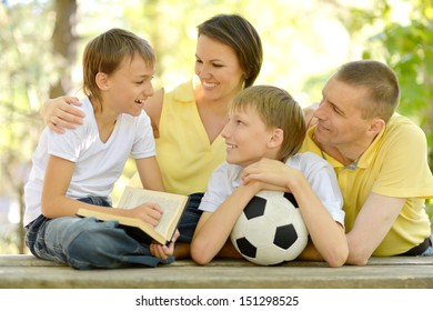 Family and socker ball. One of the boys reading