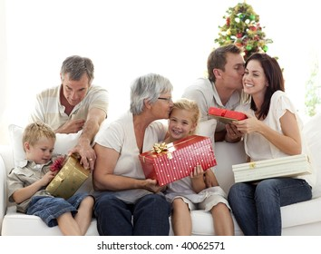 Family in sofa giving presents for Christmas