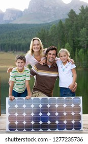Family with solar panel on jetty by lake at camera