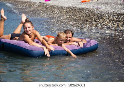 Family with son floating on an air mattress in the sea at the beach background