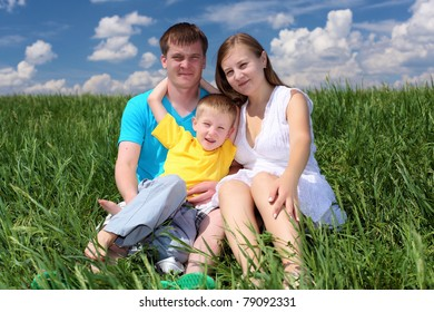 family with son in summer day on the meadow