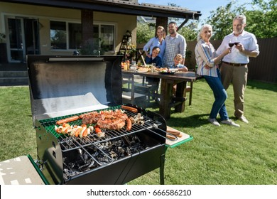 family spend time together while having barbecue with grill at yard