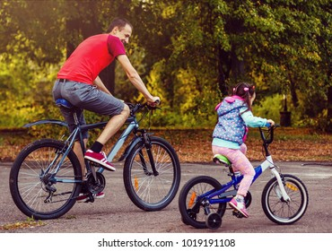 Family sport father and daughter riding bikes in green forest