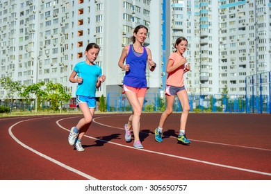 Family sport, happy active mother and kids jogging on track, running and working out on stadium in modern city