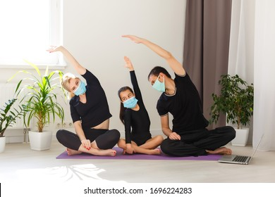 family in sportswear watching online video on laptop and doing fitness exercises at home. Distant training with personal trainer, social distance or self-isolation, online education concept