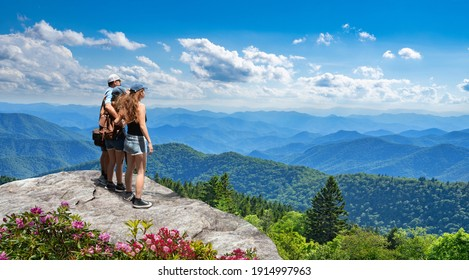 Family standing with arms around on top of mountain, looking at beautiful summer mountain landscape. People enjoying view. Smoky Mountains in background. Near Asheaville, North Carolina, USA.
