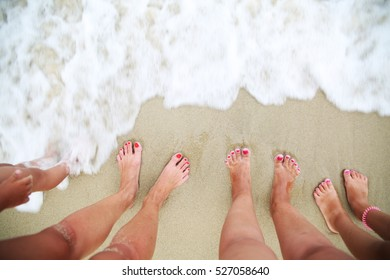 Family standing barefoot on sandy beach