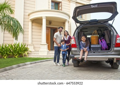 Family standing beside open boot of parked car to go on vacation