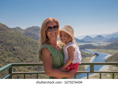 Family standing and fave fun at viewpoint of Rieka Crnojevica, Montenegro. MOther with little daughter enjoy view on skadar lake.