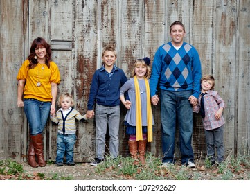 Family standing in front of a wooden fence