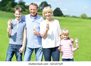 Family standing at grass field with ice cream and smiling