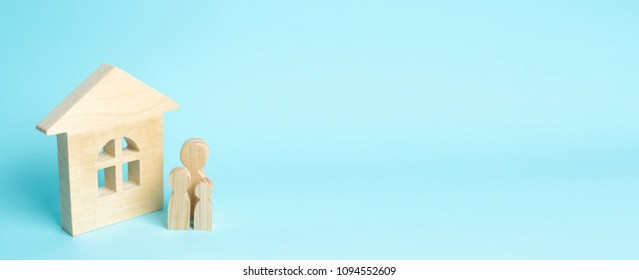 Family is standing near the house. Wooden figures of persons stand near a wooden house. The concept of a couple in love, cohabitants, parents, buyers and sellers at home. They live in house. banner.