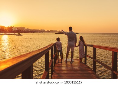 Family is standing on the beach, everyone is dressed in white clothes, dad is holding his son and daughter for here.