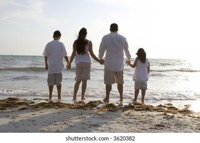 Family standing on a beach, looking towards the water