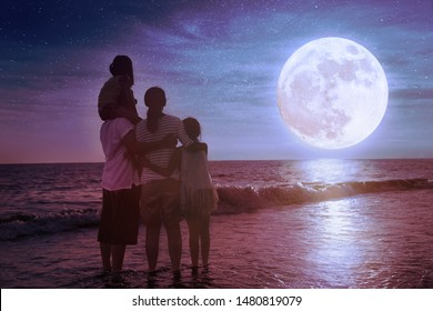 family standing on beach and watching the moon.Celebrate Mid-autumn festival together