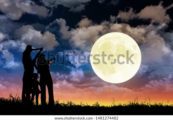 family standing on hill and watching the moon.Celebrate Mid-autumn festival together