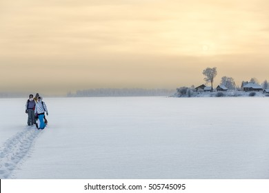 Family standing on ice of frozen lake while hiking to home, copy space