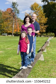 Family standing on a log during the fall