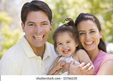 Family standing outdoors smiling