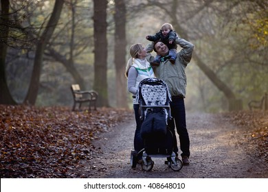 A family standing in the park, father carrying his son on his shoulders