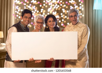 Family standing with a white board in hand on Diwali