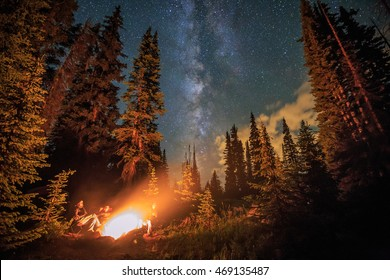 Family stargazing by a campfire, Colorado Rockies, USA.