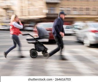 Family with stroller on zebra crossing in motion blur