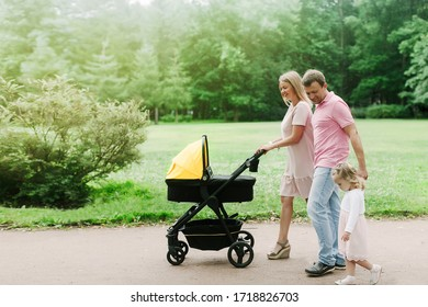 family with a stroller walking in the park on a summer day, family on the weekend