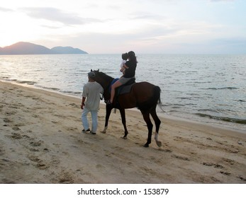 Family Strolling on Beach with Horse during Dusk