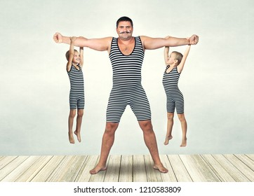 Family of strongman. The father of two sons in vintage costume of athletes perform strength exercises. Family look.