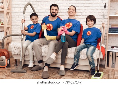 The family in suits of superheroes poses on the camera at home. Mom, Dad, son and daughter are cleaning the house.