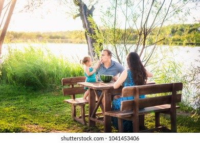 Family in summer on a picnic near a pond, water. Family holiday in nature. A little daughter feeds her father with a piece of watermelon. Unplugged mindfull.