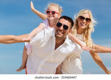 family, summer vacation, adoption and people concept - happy man, woman and little girl in sunglasses having fun over blue sky background