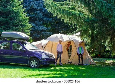 Family summer vacation in the coniferus forest with a tent.