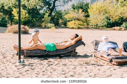 Family sunbathing on beach - Cirali, Antalya Province, Turkey