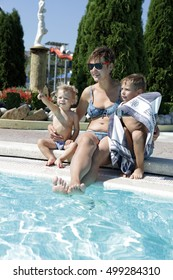 Family sunbathing on edge of pool in aquapark