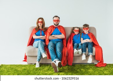 family in superhero costumes sitting with crossed arms and looking at camera on grey