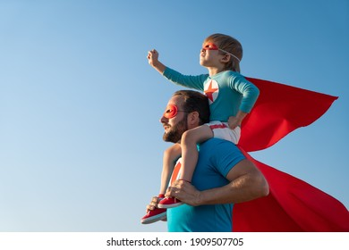 Family of superheroes having fun outdoor. Father and son playing against blue summer sky background. Imagination and freedom concept